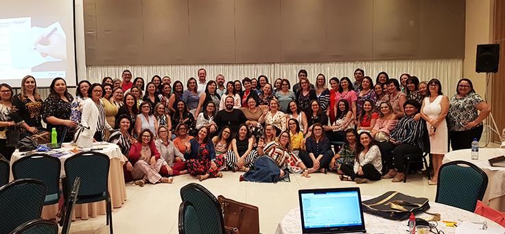 Participantes de formação no Rio Grande do Norte da Assessoria Inova Escola, que promove inovação educativa na rede pública, formam grupo de cerca de 50 pessoas, sentadas lado a lado em três fileiras, dentro de auditório.
