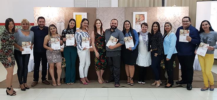 Grupo com 14 homens e mulheres lado a lado posa segurando material de formação da Assessoria Inova Escola, que promove inovação educativa na rede pública, no Rio Grande do Norte.