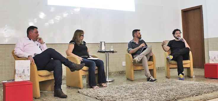 Quatro pessoas estão sentadas em poltronas em cima de palco durante formação da Assessoria Inova Escola, que promove inovação educativa na rede pública, em Goiás. Uma delas está falando ao microfone.