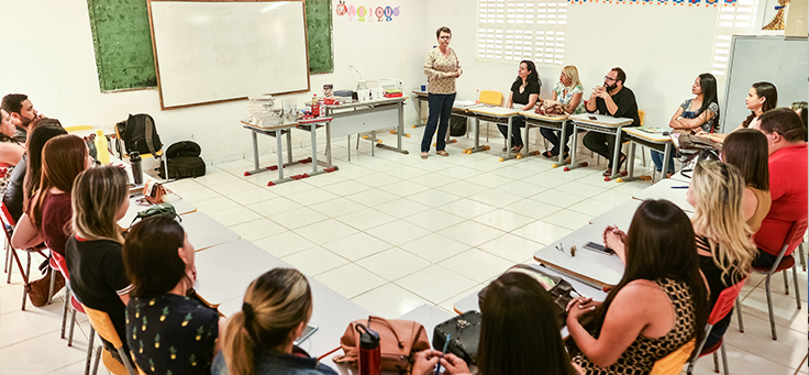 Cerca de 20 pessoas estão sentadas em carteiras, formando um círculo, durante formação da Assessoria Inova Escola, que promove inovação educativa na rede pública, em Saloá-PE. Uma delas está em pé, falando em frente a um quadro negro.
