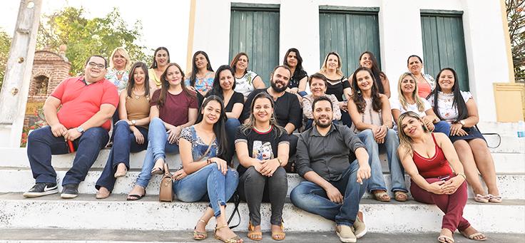 Grupo de 21 pessoas entre educadores e apoiadores do projeto Assessoria Inova Escola, que promove inovação educativa na rede pública, posa para foto em Saloá-PE. Eles estão sentados em degraus em frente a uma casa com janelas verdes.