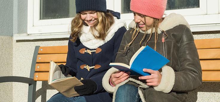 Educação na Finlândia incentiva a leitura de livros. Na imagem, duas mulheres estão sentadas lado a lado com livros nas mãos. Elas usam casacos de inverno.
