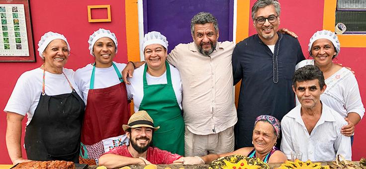 Manish Jain posa para foto com um grupo formado por cinco mulheres e três homens. Eles usam roupas próprias de cozinheiros.
