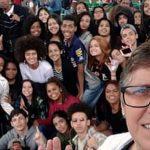 Alunos e professores da Escola Estadual Professor Joaquim Luiz de Brito posam em festival contra homofobia. Um homem de óculos aparece em primeiro plano com o grupo de alunos atrás dele.