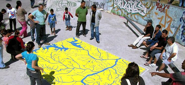 Grupo de participantes e idealizadores estão reunidos em volta de mapa que mostra os rios da cidade de São Paulo. Rios e Ruas é um dos projetos que remodelam a relação entre cidades e pessoas.