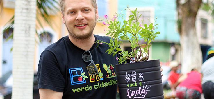 O engenheiro agrônomo Daniel Oliveira está sorrindo para a foto e segurando um vaso com uma planta. O Verde Cidadão é um dos projetos que remodelam a relação entre cidades e pessoas.