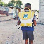 Na imagem menino está usando a bolsa do projeto Repurpose Schoolbags, que auxilia na educação de crianças, enquanto anda por rua sem asfalto.