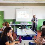 Beto Silva fala para professores sentados em grupos durante palestra formativa da Assessoria Plugada, iniciativa da Fundação Telefônica Vivo que atua para fortalecer a inovação educativa em redes públicas.
