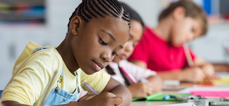 Menino está sentado em uma carteira escrevendo em um caderno. Imagem ilustra texto sobre pensadores que embasam o conceito de inovação em educação.
