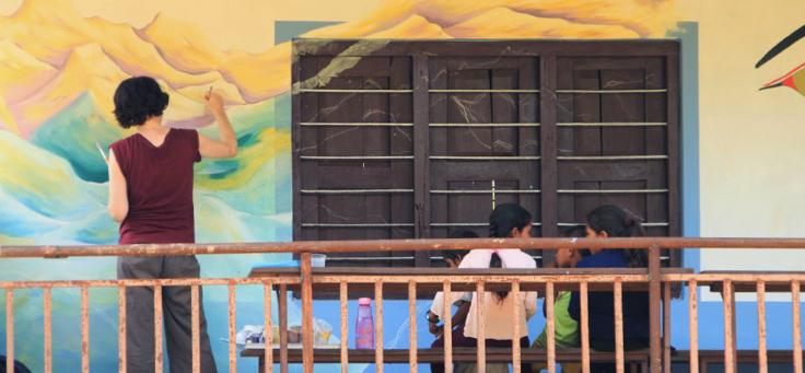 Mulher desenha quadro em muro de escola enquanto duas meninas conversam sentadas em banco atrás dela – matéria sobre volunturismo foi destaque em Voluntariado em 2018.