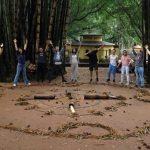 Na imagem, alunos realizam uma performance em um jardim, inspirados por artistas plásticos brasileiros.