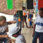 Duas alunas da Escola Municipal Gersino Coelho estão agachadas e de mãos dadas em demonstração de brincadeiras que resgatam culturas marginalizadas, no projeto É de Quebrada que Eu Vou.