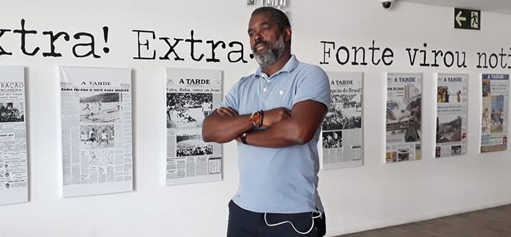 Ex-jogador João Marcelo, que participou de documentário descrito no e-book com práticas pedagógicas do CENOR, está de braços cruzados sorrindo para a foto.