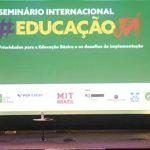 Cinco palestrantes estão sentados em cadeiras, dividindo o palco do Educação Já, seminário que debateu Educação Básica.