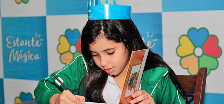 Menina usando coroa está autografando livro do Estante Mágica, projeto que publica histórias escritas por crianças.