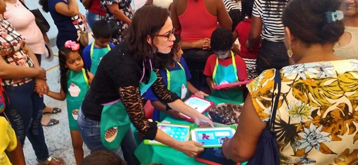 A imagem mostra a comunidade escolar interagindo com os tablets