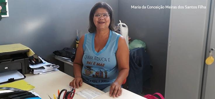 """Gestora Conceição sorri para a câmera sentada em sua mesa. Ela usa blusa azul onde se lê: """"Quem educa é pai e mãe""""."""
