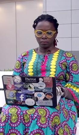 Mariéme Jamme, uma das representantes de mulheres poderosas, está com um computador no colo, usando um vestido colorido em azul, amarelo e roxo com estampa étnica.