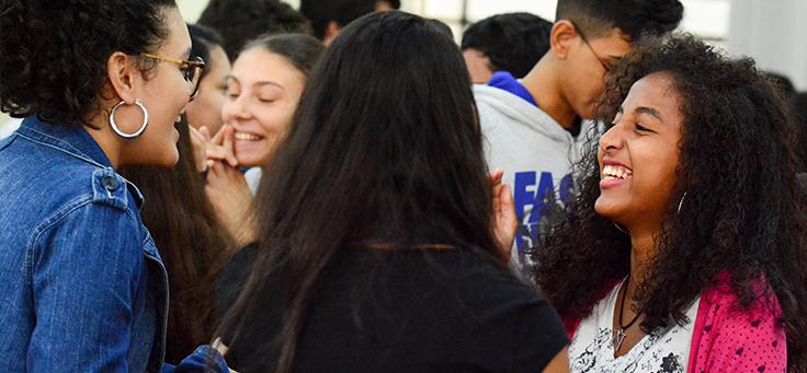 Jovens de ETECs, que participaram do programa Pense Grande estão em roda sorrindo. A estratégia Sensibilizar inclui o Pense Grande.doc e o Pense Grande Podcast.