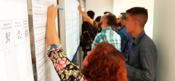 A imagem mostra pessoas de costas escrevendo em um quadro branco, com destaque para uma mulher, de camisa florida, em primeiro plano.