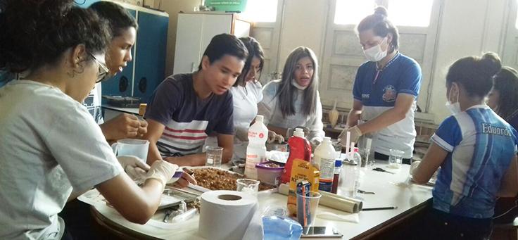 Grupo de alunos está sentado em torno de uma bancada com elementos usados para experimento, como álcool e alimentos, em laboratório da Escola Estadual Nossa Senhora de Nazaré, em Manacapuru (AM).