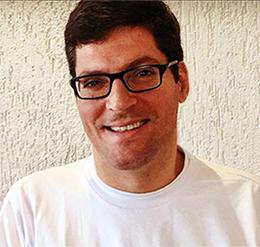 Rodrigo Hübner Mendes está usando óculos e camiseta branca e olhando para foto. O brasileiro falou em conferência anual da ONU sobre Síndrome de Down.