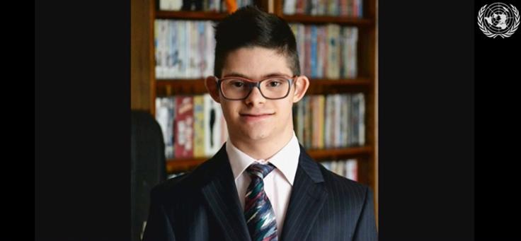 Jovem Samuel, que tem Síndrome de down, está usando terno e gravata em cerimônia anual da ONU sobre educação inclusiva.