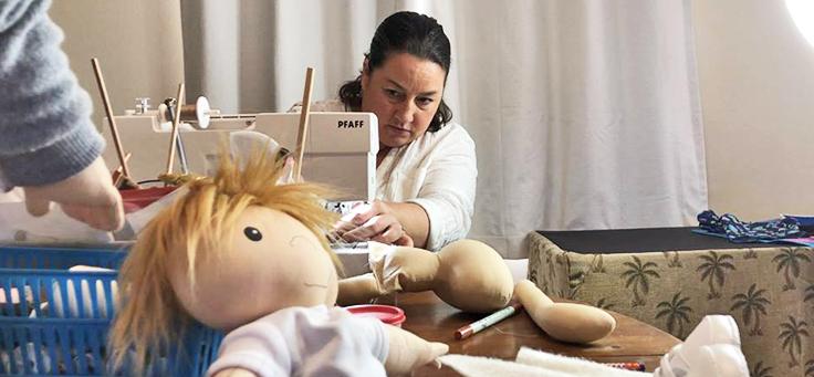 Amy Jandrisevits aparece na imagem costurando em uma máquina de costuras. Uma boneca está em primeiro plano
