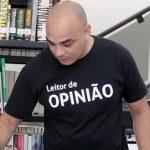 Edson Moura, criador de projeto para democratizar o acesso à leitura, está em pé, usando uma camiseta com a frase Leitores de Opinião e com livros ao fundo