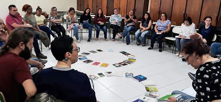 Formação de cultura de paz do Núcleo de Educação para Paz (NEP) mostra pessoas sentadas em carteiras formando um círculo em uma sala de aula.