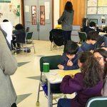 Imagem mostra alunos sentados em duplas sendo orientados por educadores para ilustrar pauta sobre ensino de matemática.