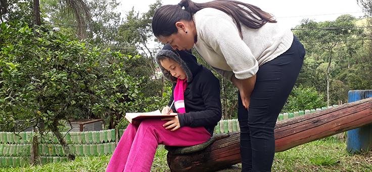 Educadora está lendo livro com aluna sentada em um banco de madeira na Escola Municipal de Mirantão, que integra lista das mais inovadoras do Brasil.
