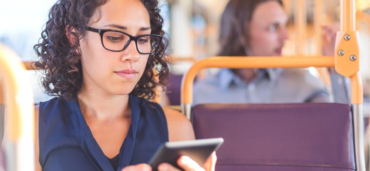 Mulher de cabelos enrolados e óculos está olhando para tela de smartphone em um banco de ônibus. Imagem ilustra pauta sobre como educação midiática combate as fake news.