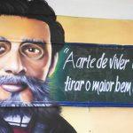 Imagem do escritor Machado de Assis, usando óculos, barba e cavanhaque estampa uma das paredes de escola em Guarulhos no projeto Grafite na Escola.