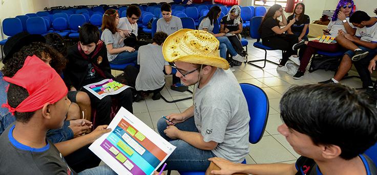 Estudantes usando chapéus estão sentados frente a frente olhando para um canvas impresso em um papel sulfite. A metodologia do Pense Grande ensina atividades sobre cultura empreendedora.