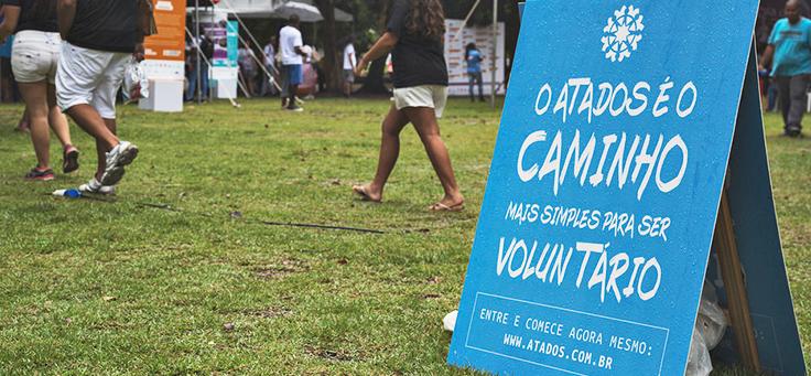 Placa do Atados, incentivando a inscrição para trabalho voluntário, está colocada em gramado.