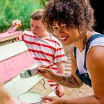 Jovem de cabelos encaracolados está sorrindo enquanto pinta uma placa. Lista traz possibilidades de trabalho voluntário.