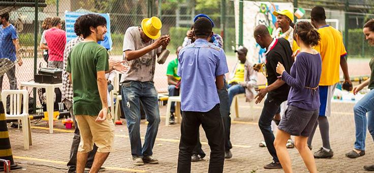 Voluntários e refugiados estão dançando em roda durante atividade promovida pelo Instituto Adus.