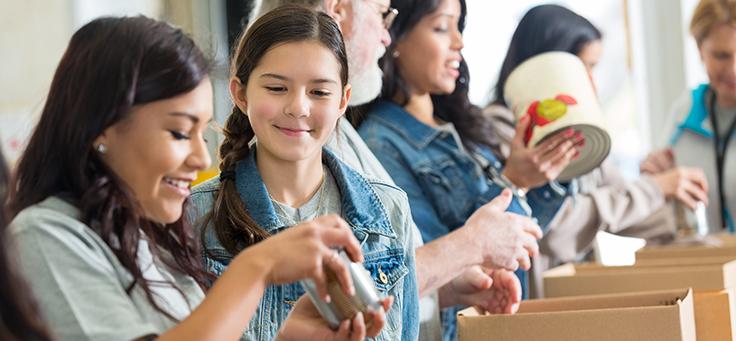Adolescentes estão em primeiro plano empacotando objetos durante trabalho voluntário.