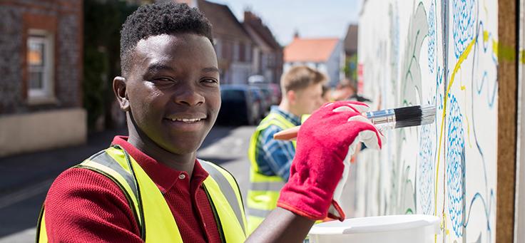 Jovem negro está sorrindo para a foto e pintando muro durante ação em trabalho voluntário