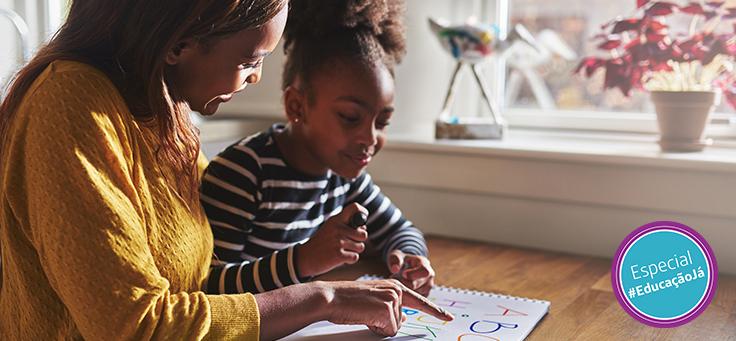 Imagem mostra uma mulher com uma criança olhando para uma apostila em cima de uma mesa de madeira
