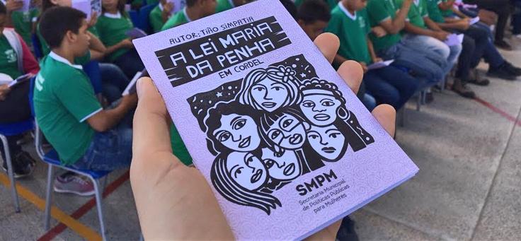 Em primeiro plano uma mão segura e mostra a capa da versão em cordel, onde estão ilustradas sete mulheres de várias etnias, de obra que narra a Lei Maria da Penha para jovens de escolas no Ceará.