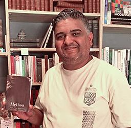Paulo César Marciano, o PC, idealizador da Editora Gráfica Heliópolis, está segurando o primeiro livro publicado dele, Melissa, com uma estante com livros ao fundo.