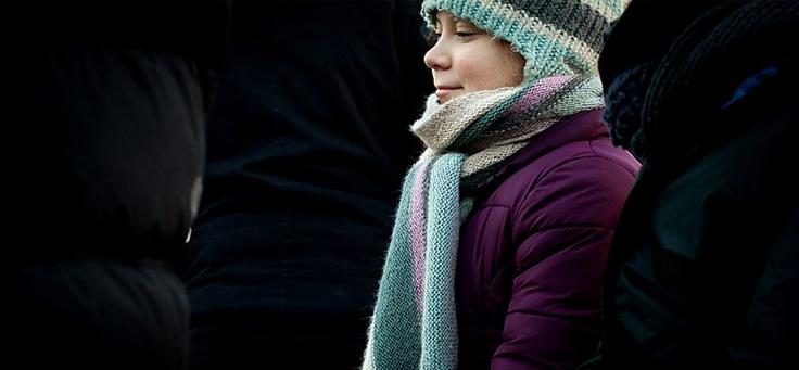Na imagem, Greta Thunberg, jovem ativista de 16 anos que ganhou fama mundial por lutar em temas ligados à mudança climática, está usando gorro e cachecol em tons azul e lilás.