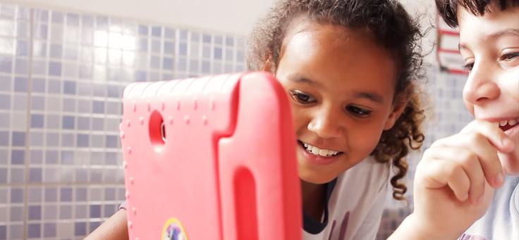 Imagem mostra duas crianças olhando para um tablete e sorrindo