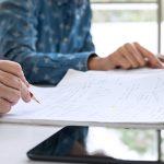 A imagem mostra o detalhe de uma mão escrevendo em uma folha de papel
