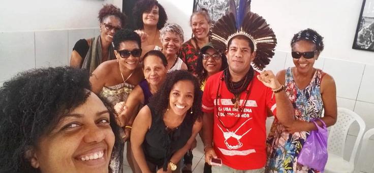Integrantes do coletivo feminista da Feira das Mulheres de Itapuã estão sorrindo para a câmera. Em primeiro plano, uma mulher de cabelos encaracolados está tirando a selfie e um dos integrantes usa cocar.