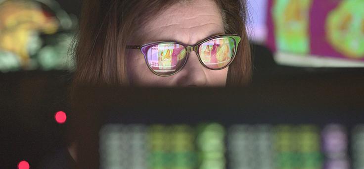 Imagem mostra mulher de óculos sentada atrás da tela de um computador