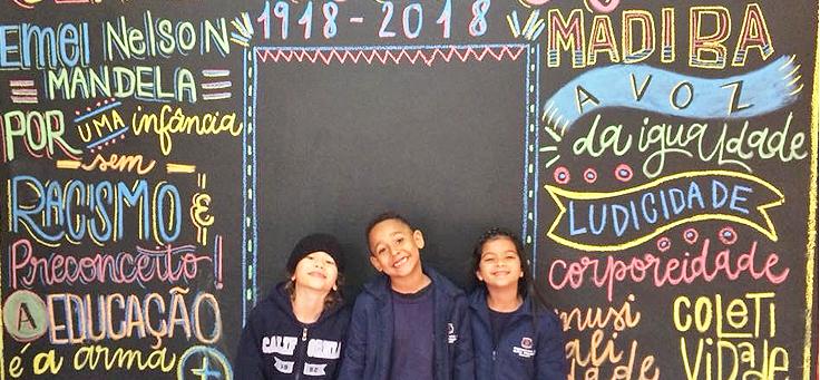 """Três alunos estão encostado em muro da EMEI Nelson Mandela, onde estão escritas em letras coloridas frases sobre ensinamentos do líder sul-africano que dá nome a escola, como """"Por uma infância sem racismo e preconceito"""" e """"Educação é a arma""""."""