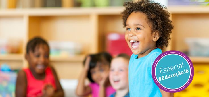 Menino de cabelos cacheados e blusa azul está em primeiro plano, sorrindo para a foto, representando crianças de 0 a 6 anos, faixa etária que corresponde à Primeira Infância.